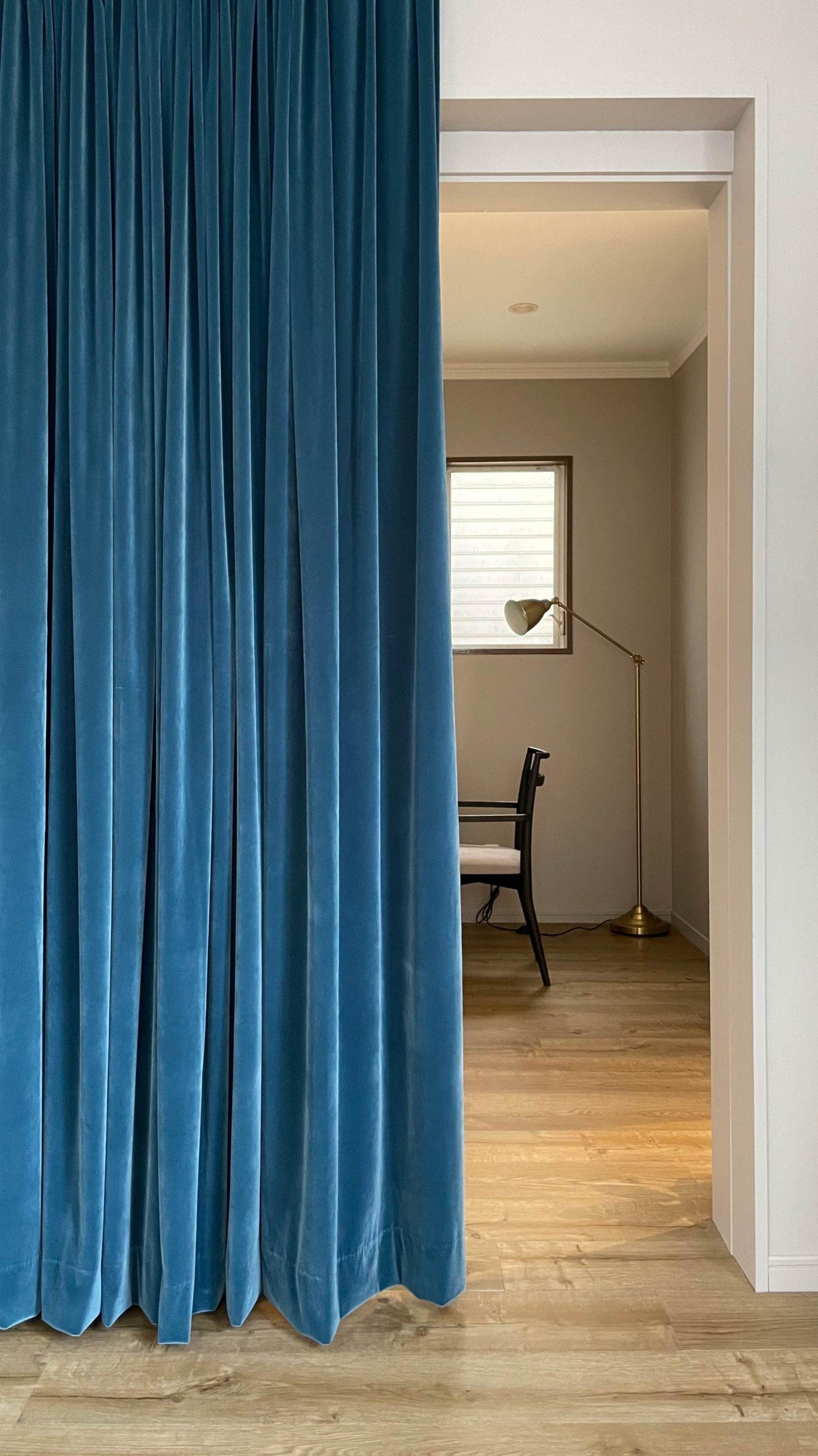 アルゴリズムがコーディネートを手がけたサロンの施術室の深いブルーのカーテン
